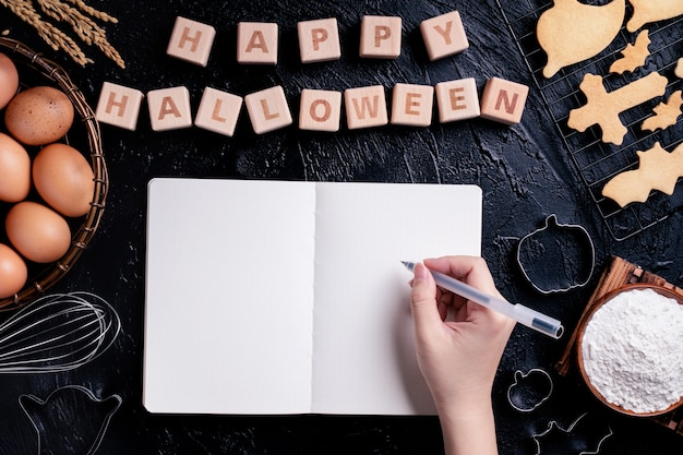 Young woman is reading and writing recipe of making halloween cookies, design concept of preparing for halloween party, top view, flat lay, overhead.