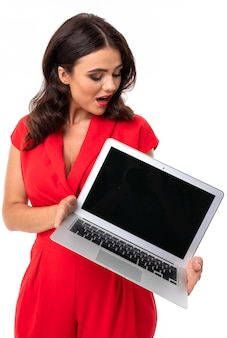 Young woman is red lips, bright makeup, dark wavy long hair, in a red suit, standing with a white laptop