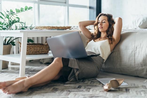 若い女性はリラックスして家でラップトップを使用しています。