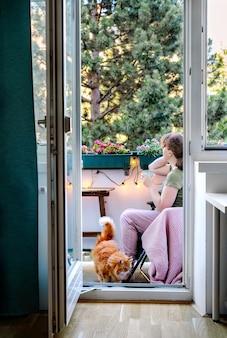 젊은 여성이 발코니에서 휴식을 취하고 있다