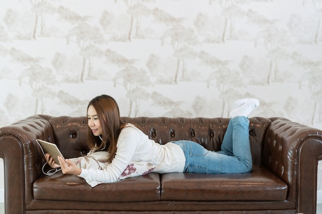 Young woman is relaxing on comfortable couch and using tablet at home.
