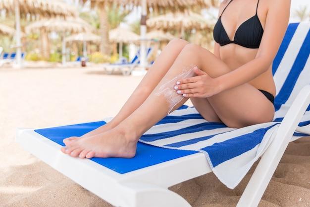 Молодая женщина расслабляется на шезлонге на пляже и наносит лосьон для загара на ногу рукой.