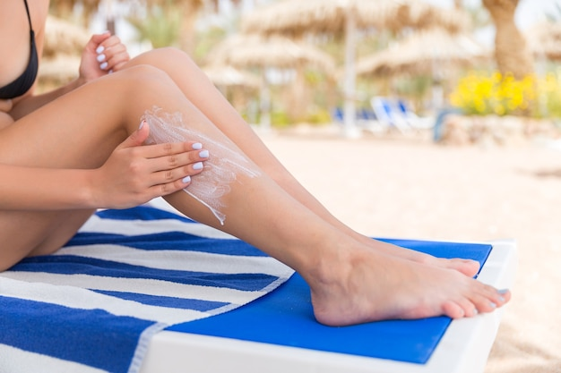 Young woman is relaxing on the sunbed at the beach and applying sun lotion on her leg with her hand.