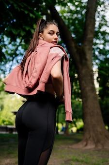 若い女性は公園でジョギングした後休んでいます。