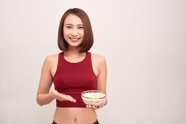 젊은 여자는 휴식과 운동 후 건강한 오트밀을 먹고있다.