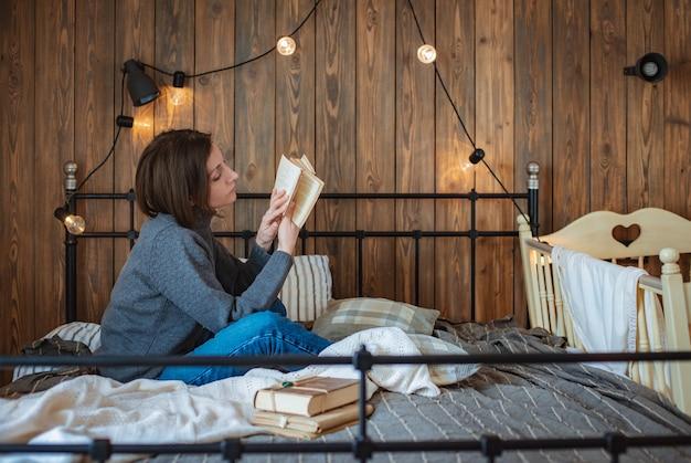 Молодая женщина отдыхает дома на кровати и читает книгу возле детской кроватки. мама отдыхает. тихий час деревянный фон гирлянда лампочки