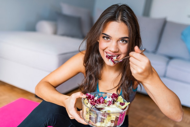 Young  woman is resting and eating a healthy salad after a workout and blinking her eyes a