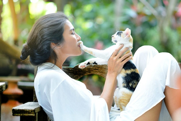 Young woman is resting with a cat on the armchair in the garden