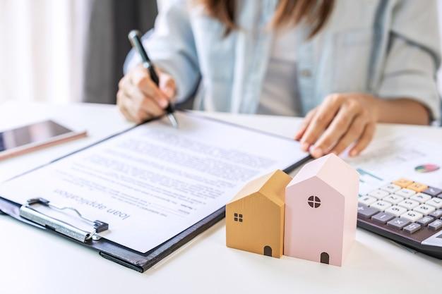 젊은 여성이 부동산 중개인 사무실에서 새 집을 사기 위해 대출 계약에 서명하고 있습니다.
