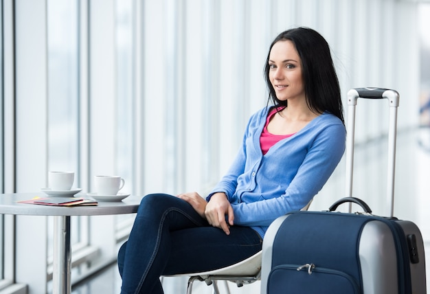 Young woman is sitting in the airport with coffee.