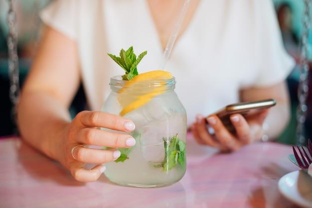 若い女性は、夏の日にテーブルに座って、ミントとレモンのスライスを片手に冷たいレモネードを持ち、自分の携帯電話を見ています。日常生活の最新技術休息とリラクゼーション