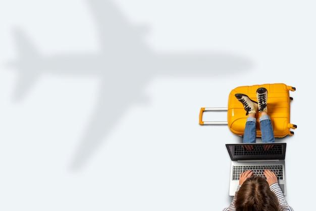 若い女性が飛行を待っている空港に座っています