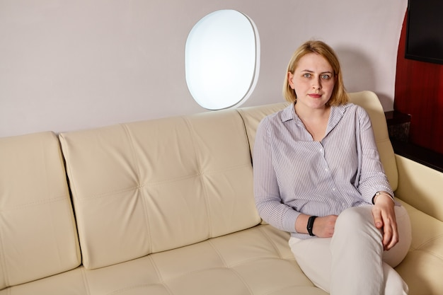 Young woman is sitting in business class of airplane near porthole.