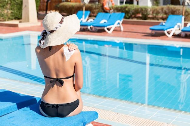 Молодая женщина сидит у бассейна и наносит крем для загара на плечо у бассейна. фактор защиты от солнца в отпуске, концепция.