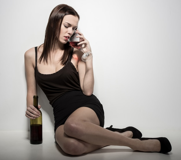 A young woman is sitting on the floor with a glass of wine.