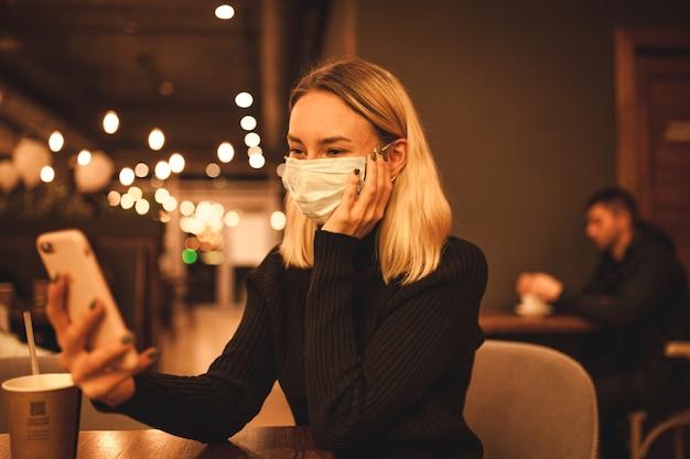 Молодая женщина сидит в кафе блондинка женщина в маске время карантина