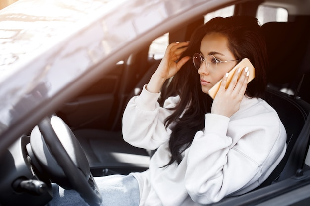 若い女性は車に座っています。美しいブルネットのモデルは、スマートフォンや電話を使用しています