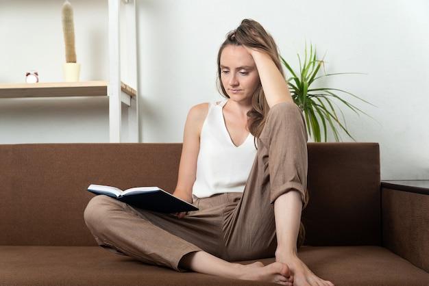 Молодая женщина сидит на диване и читает книгу. досуг дома.