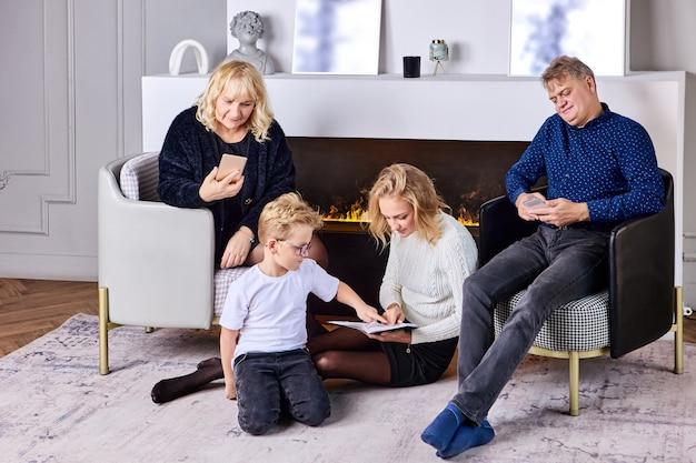 젊은 여자는 근처에 아들과 부모와 함께 책과 함께 바닥에 앉아있다