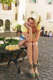 若い女性は、レモンのストリングバッグと木の陰でベンチに座っています