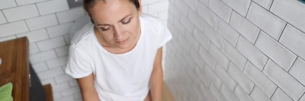 若い女性は目を閉じてトイレに座っています