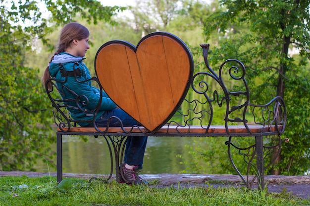 Young woman is sitting and waiting on a bench