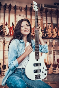 Young woman is sitting with electric guitar in music store.