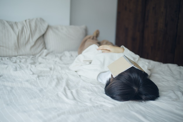 Young woman is sleeping after read book on her day-off.