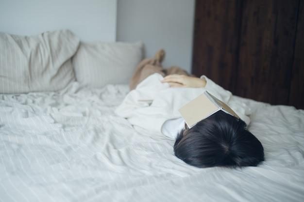 Молодая женщина спит после прочитанной книги на ее выходной.