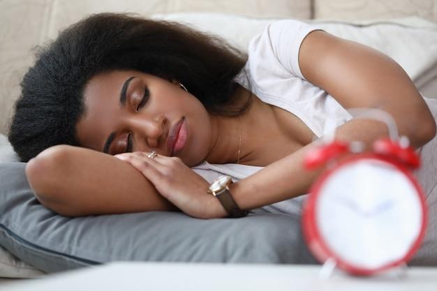 Молодая женщина спит будильник на столе