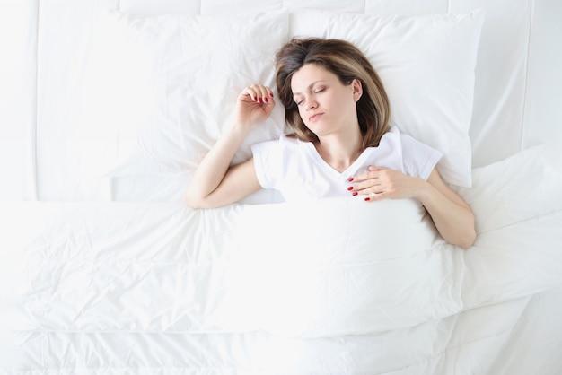 若い女性は大きな白いベッドで寝ています