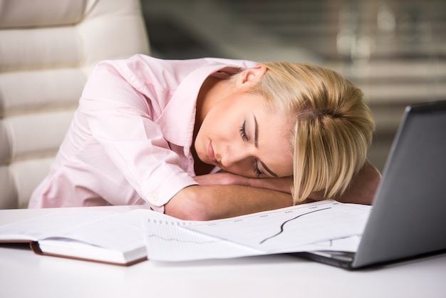 Young woman is sleeping at workplace.