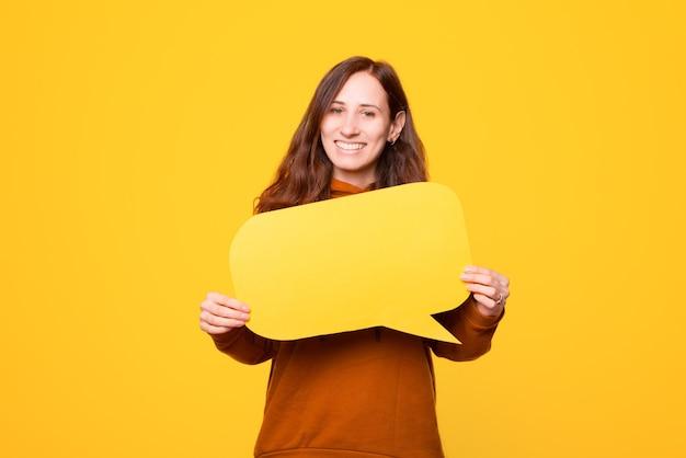 Молодая женщина улыбается и держит речевой пузырь
