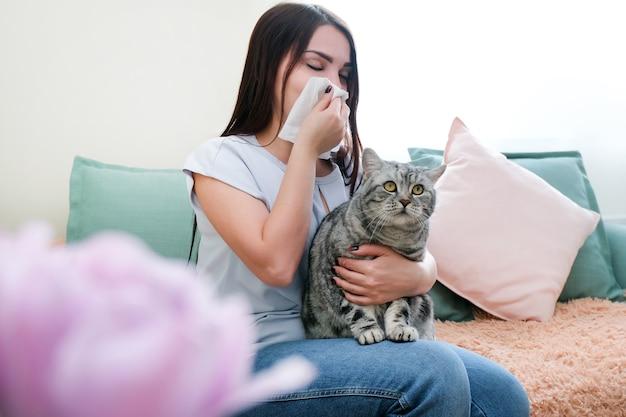 Молодая женщина чихает от аллергии на мех на диване и играет со своей кошкой.