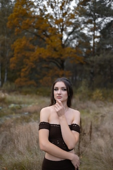 A young woman is standing in a forest, enjoying carefree autumn day in the nature. autumn portrait