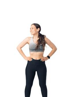 若い女性はスーパーヒーローの姿勢で立っています。彼女はスポーツウェアとイヤーポッドを着ています。