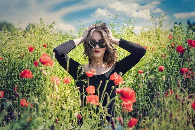 Молодая женщина стоит возле цветущего макового поля