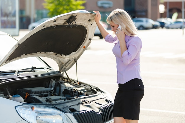 Young woman is standing near her broken car
