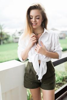 Молодая женщина стоит на балконе и смотрит вперед. на террасе отдыхает стройная женщина.