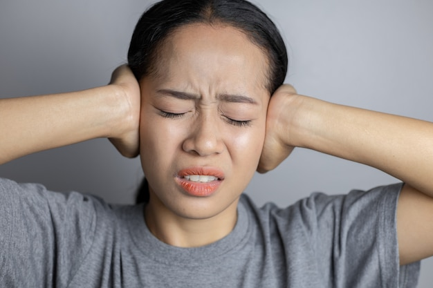 Young woman is suffering of earache.