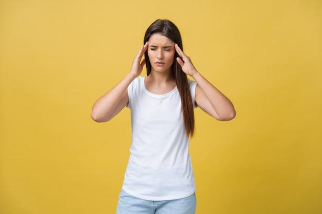 若い女性は、黄色の背景に対して頭痛に苦しんでいます。スタジオショット。