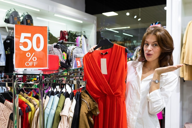 A young woman is surprised by a beautiful red dress on a discount.