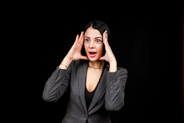 Young woman is surprised. the girl wear casual grey jacket on a black space. evil woman, hands on her sides.