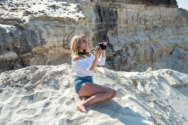 若い女性が写真の峡谷や砂の岩を撮っています