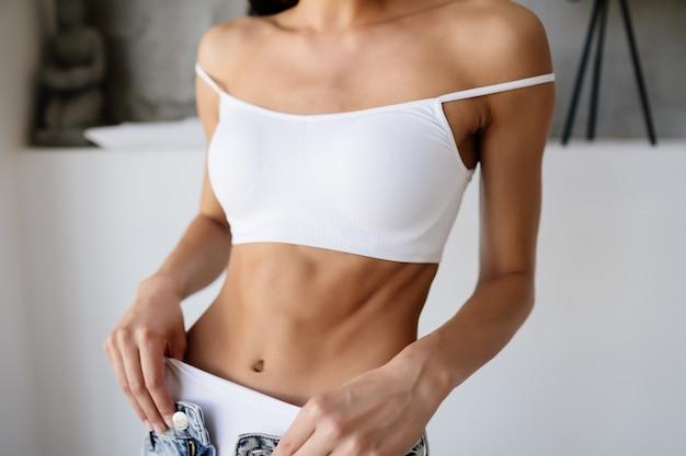 젊은 여자는 그녀의 청바지를 벗고있다.