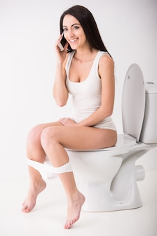 Young woman is talking by phone while seated on toilet.