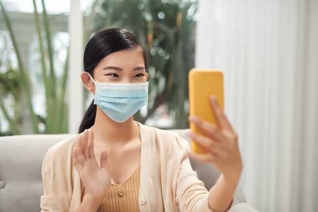 若い女性がマスクでビデオ通話で話している。在宅勤務、友達との会話、マスクでの自撮り