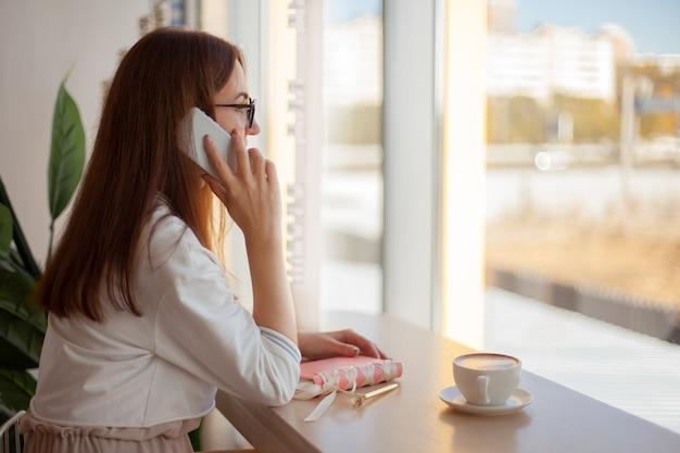 젊은여자가 전화 통화 및 메모 작성