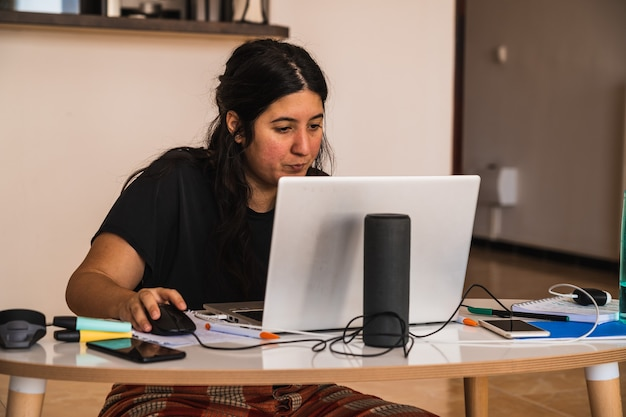 若い女性は自宅で在宅勤務しており、半分はパジャマを着ています。