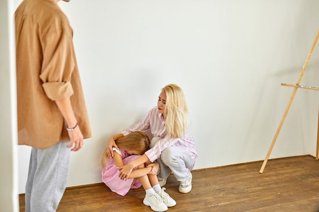 Young woman is tired of enduring humiliation from her husband at home in the presence of child girl, going to be divorced, conflict in the family